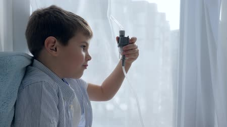 respiração : Treats inflammation of airways, inhaler tube in mouth of sick child sitting on windowsill of hospital close-up