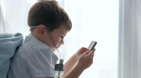 respiração : inhalation medication, boy in mask from an inhaler with cell phone into hands inside