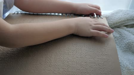 impaired : education of blind, ill kid reading book written in Braille close-up