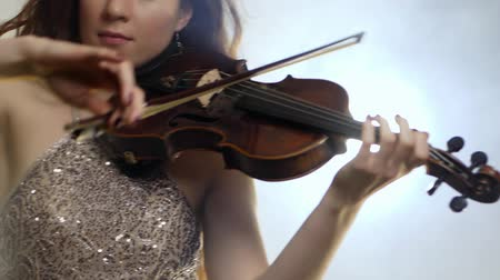 com cordas : concert of classical music, woman violinist in shining dresses playing on fiddle close-up in fog Stock Footage