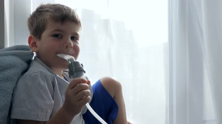 respiração : asthma treatment, child breathes through inhaler sitting on windowsill in hospital