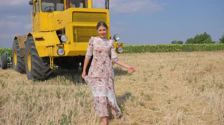 trator : young woman in dress walking barefoot along field in slow motion on background agricultural machine
