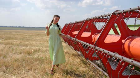 alfândega : cute girl in going in slow motion near agricultural machinery on background golden field and blue sky Stock Footage