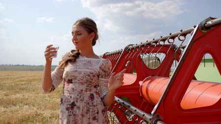 agronomist : villager female in dress drinks water and Looks into distance near Combine harvester in autumnal field