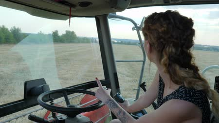 pneu : Strong female Tractor driver behind wheel of Combine harvester in field in Bread harvest season Stock Footage