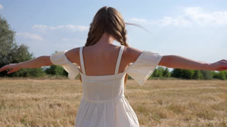 blue braid : Happy girl into white dress with braid hair turning at field in sunny day in Slow motion