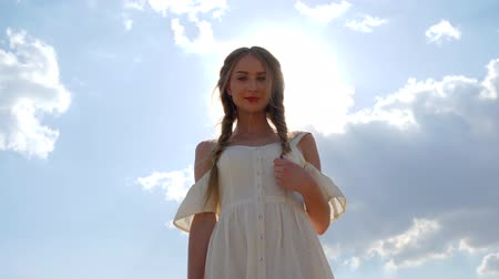 blue braid : cute woman with braid hair In white dress on background of Blue heaven In backlight close-up Stock Footage