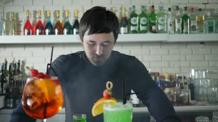 desfocado : portrait of bartender beside vivid alcohol beverage with berries on background of bar interior with colored bottles in white mist