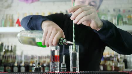 desfocado : male barman making colored drink and pours bright liquor from bottle into glass with alcohol on counter on unfocused background of bar interior