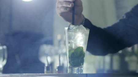 desfocado : hand of barkeeper puts plastic straws in refreshing cocktail with ice cubes and green leaves in glass standing on bar in smoke close-up