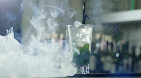 clear the table : cooling drink with ice and green mint leaves in large glass with black plastic straws stands on bar counter in smoke on unfocused background Stock Footage