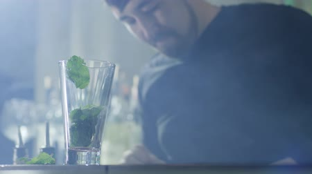 desfocado : arms of bartender with bracelet throw in transparent glass mint leaves and lime slices close-up on unfocused background