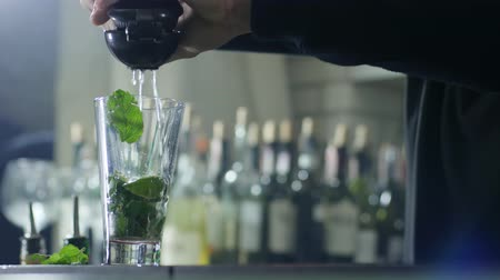 desfocado : arms of barkeeper add fresh juice in transparent glass with greenery mint and slices lime close-up on unfocused background
