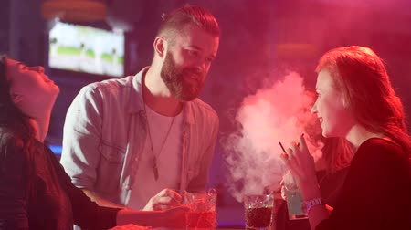 fuma : youth people having fun near table with colorful beverages in smoke on background of colored lamps at night party Vídeos