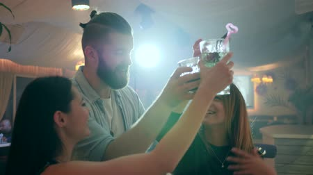 make friends : two girls and one guy have fun in a nightclub and make a toast with glasses in their hands