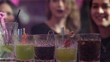 виски : glasses with colorful alcoholic cocktails and straws on the bar counter in a nightclub on background blurred people
