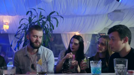 pult : company of friends holding glasses with chilled beverages on party indoors at night Stock mozgókép
