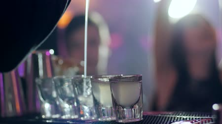 shaker : barman pours an alcoholic cocktail into the small glasses at bar counter on background of the customers