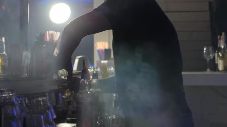 artigos de vidro : Kherson, Ukraine, 11 December 2017: bartender does cocktail near the bar stand in slow motion on background smoke in Kherson, 11 December 2017