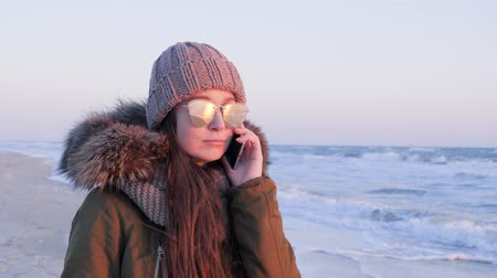 espetáculos : woman in glasses speaks on mobile on open air weekend to ocean beach in cold season