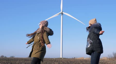 átalakítás : wind station, joyful girls spin and pose for photo near Energy Production in steppe