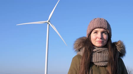 átalakítás : Wind power technology, amused girl staring into distance on background of windmill and blue sky