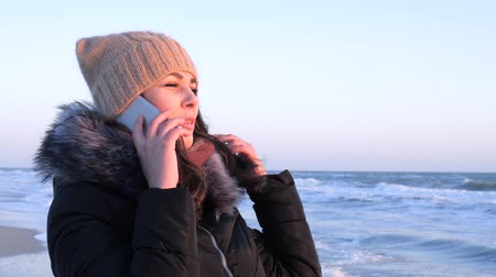 telefon : telephone communication, female speaks on smartphone in weekend at sea coast in cold season