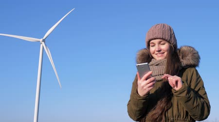 átalakítás : Internet chatting, nice female sits in social networks using mobile phone beside windmill on background sky