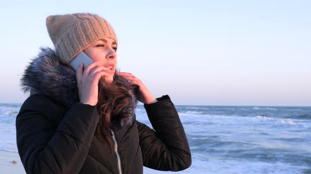 telefon : happy girl uses mobile phone to communicate with friends in vacation at seashore in cold season