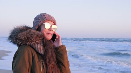 telefon : girl in eyeglasses communicates by phone outdoors at vacation on sea shore in cold season