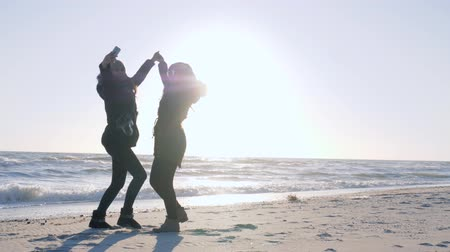 arms in the air : fun holidays, cheerful girlfriends are photographed on mobile phone at seashore in sunlight Stock Footage