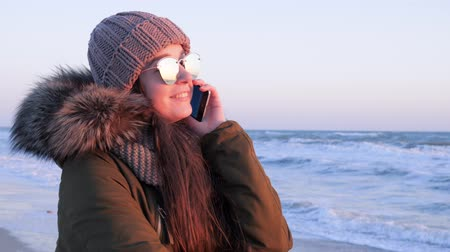 arms in the air : female into sunglasses talking on mobile phone in open air at holiday on sea coast in cold season Stock Footage