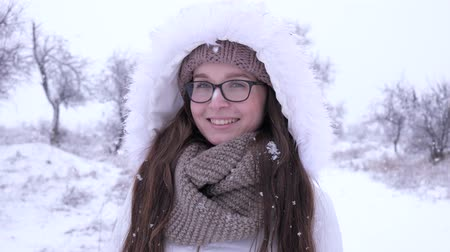 fortunate : smiling girl in eyeglasses standing under falling snow Outdoors in winter Stock Footage