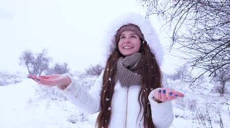fortunate : smiling girl catches snowflakes in hands and enjoys winter in nature