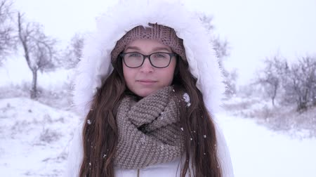 fortunate : portrait of lovely female spectacled standing under snowfall in nature in winter