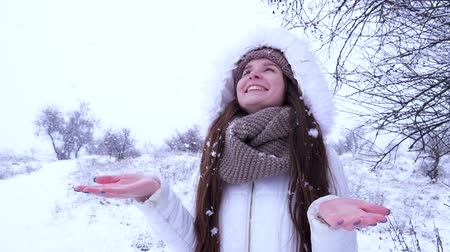 fortunate : happy woman catches falling snow in hand and smiling Outdoors in winter
