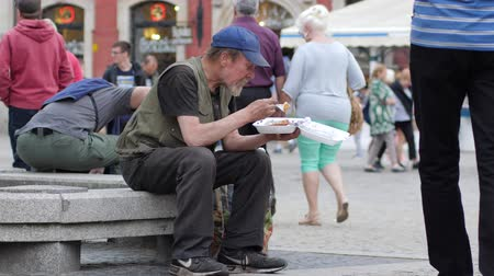 tramp : Wroclaw, Poland 12 May 2018: poor homeless man eats from plastic plate sitting on the street in Wroclaw, 12 May 2018.