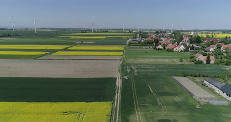 kasza jaglana : aerial view wind turbines and agricultural fields on a spring day near the village in slow motion