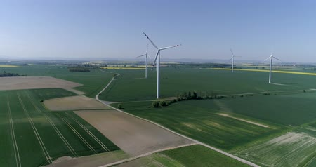 kasza jaglana : countryside with wind turbines and agricultural fields in slow motion, aerial view