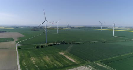 kasza jaglana : modern wind turbines generating sustainable energy on field with crop in slow motion, aerial shot