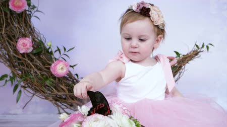 энтомология : cute little girl in pink dress points at a live big butterfly on white background with decor indoors