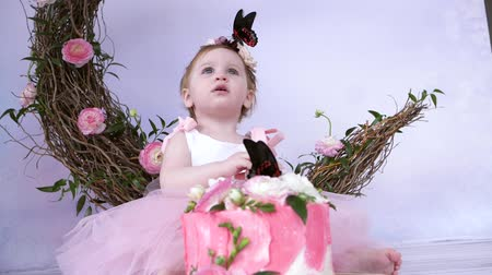 чешуекрылых : butterfly sits on the head of a beautiful small girl at photo shoot against the backdrop of a decor indoors Стоковые видеозаписи
