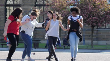 различный : Dresden, Germany 18 May 2018: weekend, young girls of different nationalities dancing holding hands and having fun outdoors in slow motion in Dresden, 18 May 2018.