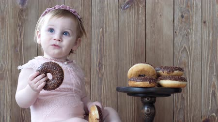 petite : food for children, infant eating sweet chocolate donuts on background of wooden wall Stock Footage