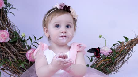 petite : dirty cute infant licks his fingers with cream close-up indoors