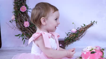 home studio : childrens birthday, happy little girl in dress with bows with cake indoors Stock Footage