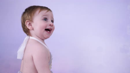 petite : baby emotions, happy toddler claps hands in bright studio close-up