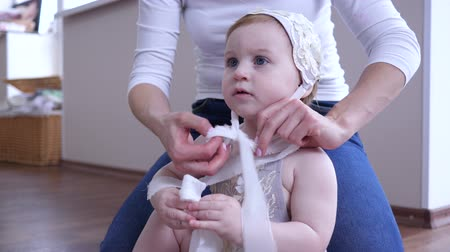szülői : baby care, mother dresses beanie on head of small daughter at home close-up Stock mozgókép
