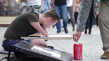 ón : Wroclaw, Poland 12 May 2018: charity, young man with hand disability draws pictures and people give money at town square in Wroclaw, 12 May 2018. Stock mozgókép