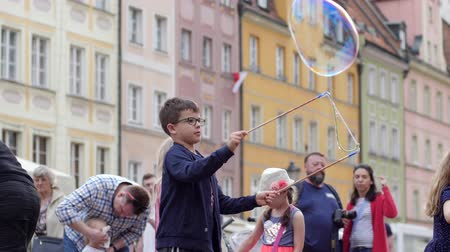 hůlky : Wroclaw, Poland 12 May 2018: cheerful childhood, cute boy plays with soap bubbles on town square in holiday in Wroclaw, 12 May 2018.